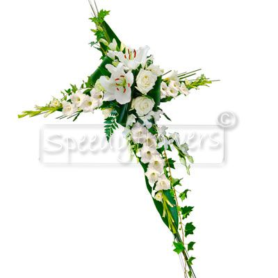 Cross of white flowers for funeral occasion.
